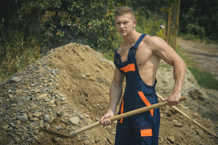 Digger concept. Manual digger man with shovel. Digger dig ground. Strong digger in working uniform Reklamní fotografie