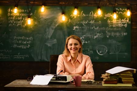 school. back to school. school teacher with retro typewriter near blackboard. woman working at typewriter in school.