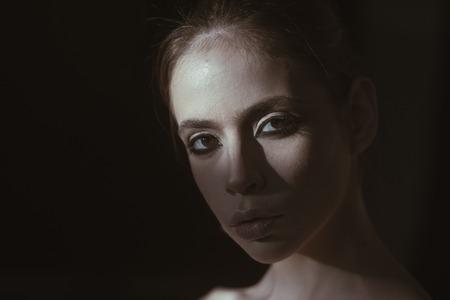 Visage de jolie femme avec maquillage dans l'obscurité. Fille mystérieuse se cachant de la lumière du jour. Portrait visage calme mystérieuse dame confiante sur fond noir. Elle est un mystère pour toi