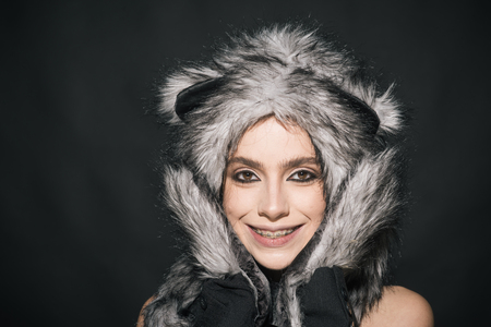 Girl with makeup wears fluffy fur hat with ears like cat. Cute kitty outfit. Carnival and Halloween ideas. Cute outfit to celebrate carnival. Woman wear furry hat with little ears like cat or kitten