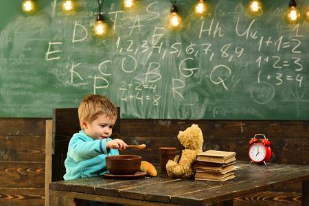 Feeding concept. Little child feeding teddy bear in school. Boy feeding and taking care of toy friend in classroom. Feeding your brain