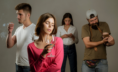 Stop alcohol addiction. Addictive group including alcohol cigarettes and drugs. Hard drugs and alcohol addict. Serious sad woman having alcohol addiction.