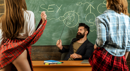 Sexy education. Bearded sexology teacher looks at two sexy female students. Erotic education and sex Symbols on chalkboard. Anatomy lesson and sex education in high school. Lets Talk Sex. Standard-Bild