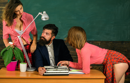Bearded sexology teacher looks at two sexy female students. Erotic education and sex Symbols on chalkboard. Anatomy lesson and sex education in high school. Lets Talk Sex. Sex education.