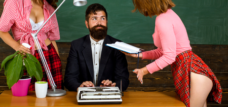 Sexy education. Bearded sexology teacher looks at two sexy female students. Erotic education and sex Symbols on chalkboard. Anatomy lesson and sex education in high school.
