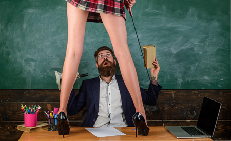 Sex education. Anatomy lesson and sex education in high school. Lets Talk Sex. Bearded sexology teacher looks at two sexy female students. Erotic education and sex Symbols on chalkboard. Stock Photo