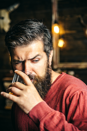 Portrait of handsome young man holding glass of cognac whiskeyand brandy. Elegant man holding a glass of alcohol drink. Handsome bearded man offers whiskey. Alcohol addiction - Social problem. Stock Photo