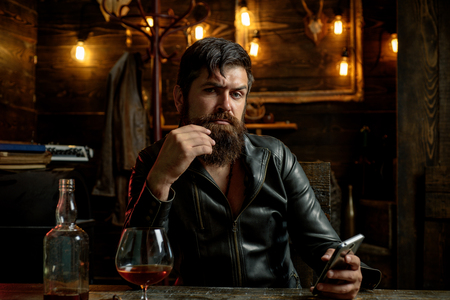 Bearded man wearing suit and drinking whiskey brandy or cognac. Sommelier tastes alcohol drink. Degustation and tasting. Portrait of young man holding glass of cognac whiskeyand brandy. Elegant man holding a glass of alcohol drink. Handsome bearded man offers whiskey. Alcohol addiction - Social problem.