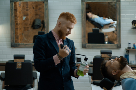 Hairdressers work for a handsome guy at the barber shop. Balm on dry body parts to moisturize skin. Moustache Wax. Sandalwood shaving cream. Professional hairstylist in barbershop interior.