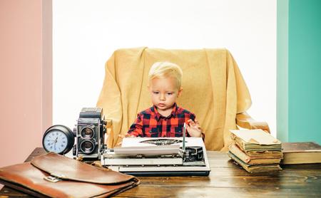 Little writer work on book at desk. Boy writer type on vintage typewriter in office.
