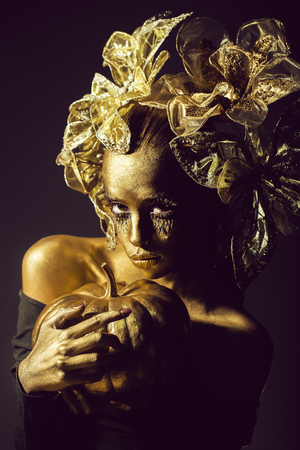 halloween golden woman or girl holding painted gold pumpkin has pretty face with makeup and body art metallized color with decorative flowers on head on black background.