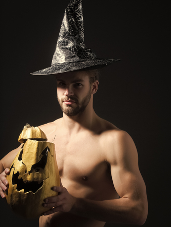 Halloween man in witch hat on black background. Macho with muscular torso, biceps, triceps holding pumpkin. Spirit and supernatural concept. Evil spell and magic. Autumn holidays and harvest season Kho ảnh