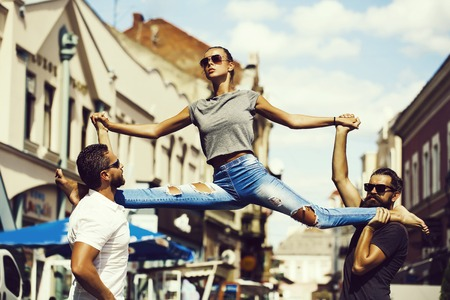 leg split of young woman standing in street training sport Фото со стока