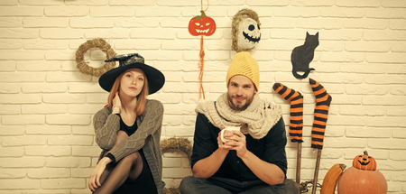 Halloween couple in love sitting on brick wall. Woman wearing witch hat. Man smiling and holding cup. Festive and homely atmosphere. Holiday celebration concept.