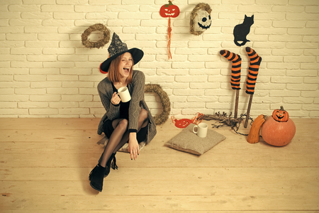 Halloween woman in witch hat winking with cups. Happy holiday celebration concept. Girl sitting on wooden floor. Coffee or tea break. Pumpkins, wreaths, mummy symbols and decorations on brick wall.