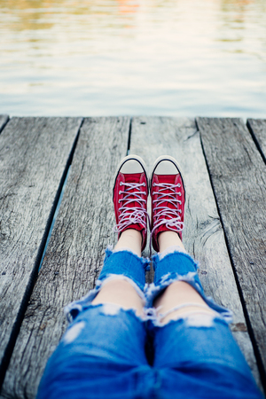 Lonely emo sitting in red sneakers. Teenage problems. Teenager dream and solitude time. Stok Fotoğraf
