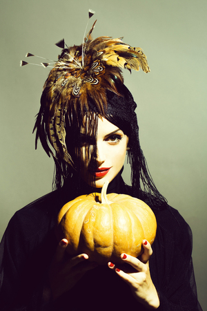 pretty sexy woman in feather hat holds pumpkin Stockfoto