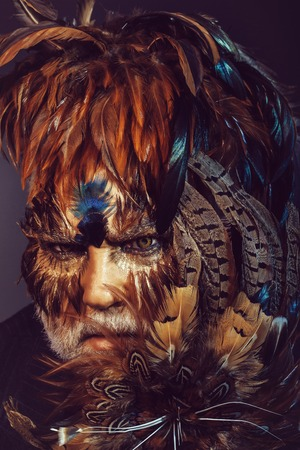 bearded old man in feather hat