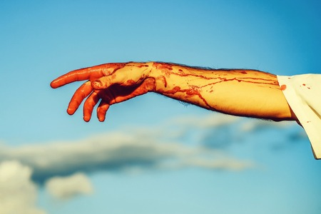 bloody zombie hand with red blood on blue sky