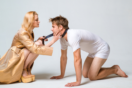 Domination and Submission. Woman and man playing domination games. Dominate obey undress seduce a partner.
