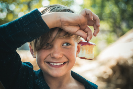 Funny little happy boy eating on a farm. Child enjoying autumn season and laughing. Happy childhood, lifestyle concept. Funny kitchen. Stock Photo