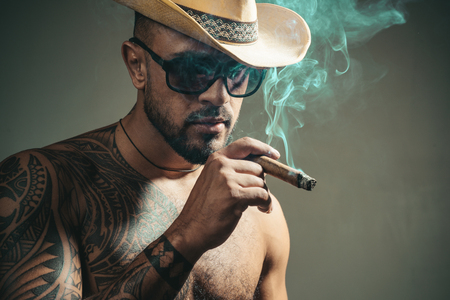 Cuban cigars. Portrait of latin face with a sensual look. Cuban man smoking cigar and enjoy life and moment. People concept. Time to enjoy.