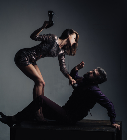 Aggressive woman holds in her hand heels. Wife argues with her husband. Be at cross-purposes. Woman holds in her hand heels. Advertising for the shoe store Фото со стока