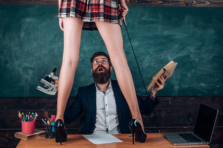 Teacher and student - love story. Sexy education. Bearded sexology teacher looks at two sexy female students. Erotic education and sex Symbols on chalkboard. Lets Talk Sex. Standard-Bild