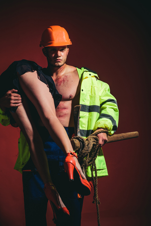 Brave Firefighter. Firefighter sexy body muscle man holding saved sexy woman. Rescuer firefighter or miners - risky occupations concept. Working profession, special clothes, overalls. Hot and sexy.