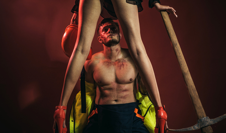 Hot sexy Firefighter. Firefighters sexy body muscle man holding saved sexy woman. Risky occupations concept. Working profession, special clothes, overalls. Hot and sexy.