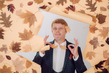 Funny red-haired man advertises your products. Banner for advertising of autumn clothes. Autumn sale.