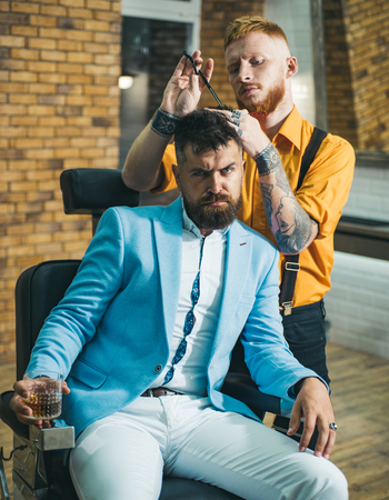 Man visiting hairstylist in barber shop. Professional hairstylist in barbershop interior. Barber - Shaves and Trims. Hair style and hair stylist.