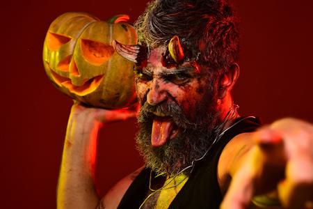 Halloween man devil hold pumpkin on red background