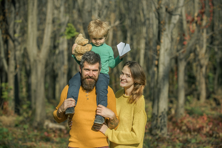 Happy family on pleasure walk in park. Happy family of father and mother with little son smile outdoor. Relaxing on nature