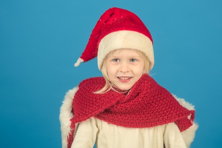 santa kid in red hat. Small santa girl with shopping package at black friday. Stock Photo
