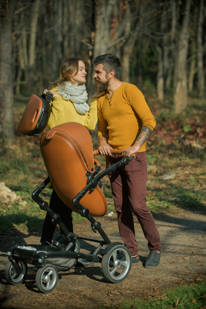 Family trust concept. Mother and father with baby pram enjoy sunny day in park, family trust. Road to life