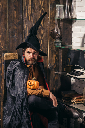 Bearded man with horror face holding Pumpkin head jack lantern on wood background. Holiday halloween with funny carnival costumes on a holiday background Imagens - 114291665