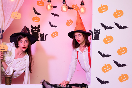 View of two halloween girls through hole in white wall. Festive halloween design. Best friends girls celebrates thanksgiving day. Halloween copy space.