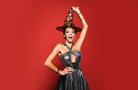 31 october - celebration party. Surprised woman in witches hat and short dress. Glamour Fashion Sexy Vampire Lady with witch costume. Stockfoto