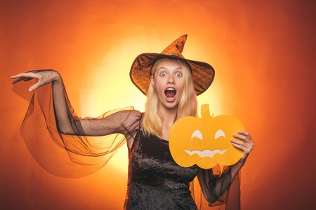 Beautiful young surprised woman in witches hat and costume pointing hand - showing products. Glamour Fashion Sexy Vampire Lady with witch costume. Celebration party. Stock Photo