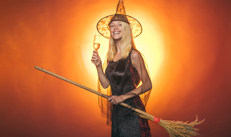Surprised woman on witches hat and costume with broom - showing products. Vampire Halloween Woman portrait. Emotional young women on halloween party over red background. Looking camera. Stock Photo