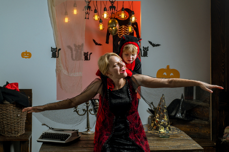 Children play with mother and have fun. Mother flies with a child on Halloween background. Witch hat for mother and son.