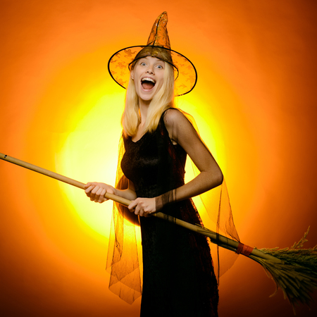 Surprised woman on witches hat and costume with broom. Vampire Halloween Woman portrait. Emotional young women on halloween party over red background. Looking camera.