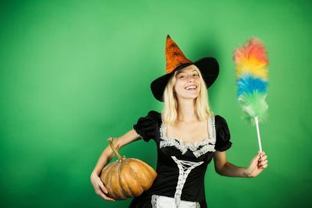 Surprised housekeeper wife with pumkin play and posing. Halloween wide banner with Sexy girl housekeeper. Costumes and witch hats.