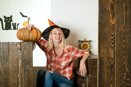 Smiling woman. Woman posing with Pumpkin. Beautiful young surprised woman in witches hat and costume holding pumpkin. Happy people.