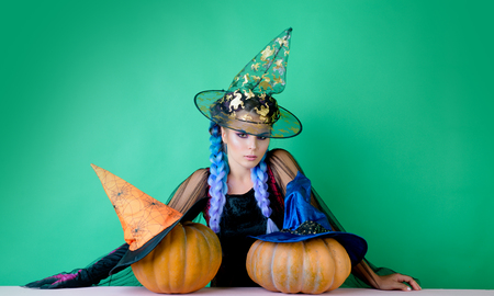 Emotional young women in halloween costumes on halloween party over green background. Looking camera. Holidays, decoration and party concept.