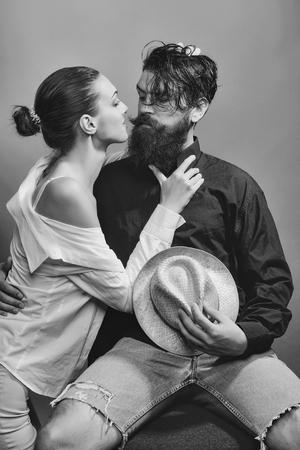 young sexy couple of woman with glamour makeup on pretty face in stylish shirt and bra kiss handsome bearded man with long beard and wet hair holding straw hat in studio on grey background.