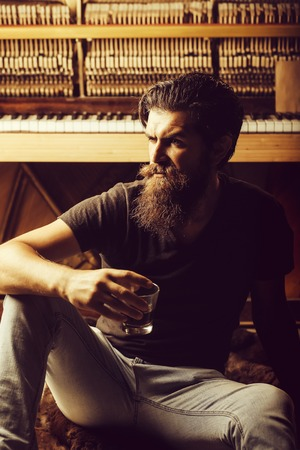 handsome bearded man with stylish hair mustache and beard on serious face drinking brandy or whiskey from glass near old wooden open piano with keyboard as musician. Stok Fotoğraf