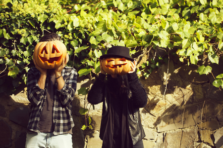young halloween couple of bearded man with beard and mustache and girl in black witch hat near stony wall with green vine with traditional autumn holiday symbol of orange spooky pumpkin outdoor. Stock Photo