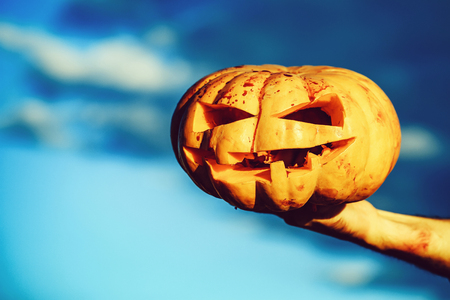 Halloween pumpkin with scary face, traditional autumn holiday symbol orange color with bloody male hand of zombie sunny outdoor on blue sky background